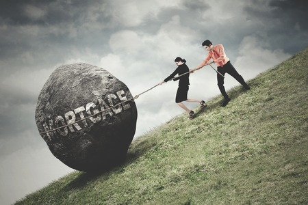 Two young business people pulling a big stone with mortgage word on the hill. Concept of big mortgage photo