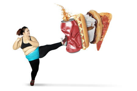 Diet Concept. Obese woman kicks a can of soft drink and fast foods while wearing sportswear. Isolated on white background