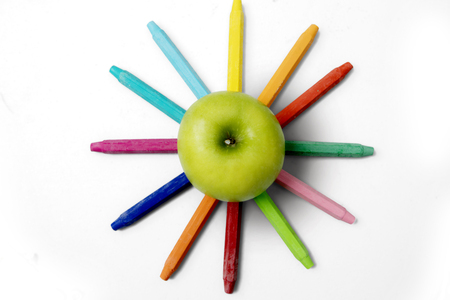 Top view of fresh apple with colorful crayons, isolated on white background