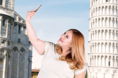 Portrait of happy woman taking selfie photo by using smartphone in front of pizza tower