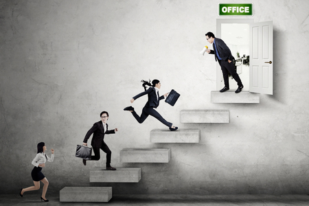 Group of young businesspeople compete on the stair by running toward the office door photo