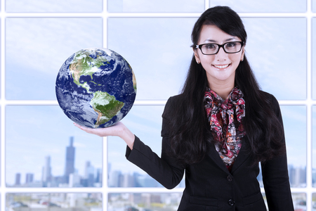 Businesswoman is holding earth in hand with cityscape background photo