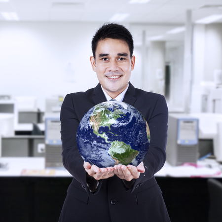 Young businessman holding the earth in his hand photo