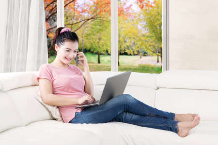 Portrait of busy woman talking by mobile phone and using a laptop while sitting on the couch photo