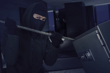 Male burglar wearing a mask and using a crowbar to open a safe deposit in the bedroom photo