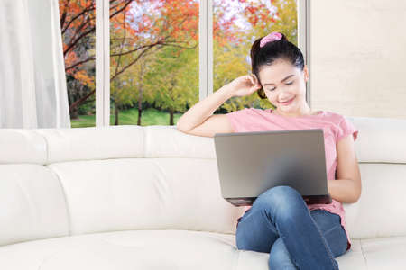 Picture of a beautiful female model relaxing in the living room while using a laptop and smiling happy, shot with autumn background on the window photo