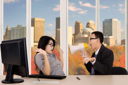 Image of male manager is screaming at his secretary through megaphone while working in the office with autumn background on the window photo