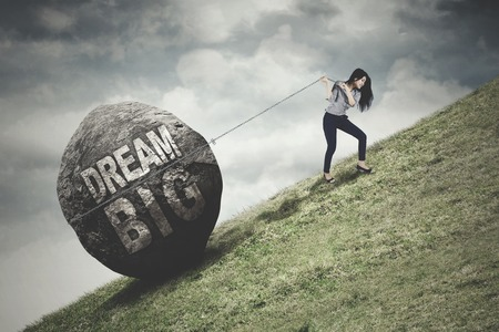 Young businesswoman climbing on the hill and uses a chain to pull a stone with Dream Big text