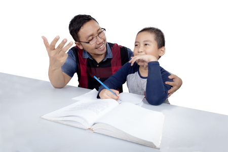 Cute little boy studying with his dad while his father help him to count, isolated on white background photo