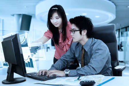 calculator chinese: Picture of a beautiful businesswoman pointing virtual growth charts on the computer screen while helping her partner in the office