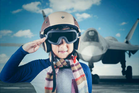 Portrait of a cute little boy wearing an aviator helmet while giving a respectful hand gesture with a jet plane background photo