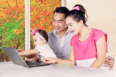 Portrait of smiling parents and cute child looking at laptop while sitting at home with autumn background on the window photo