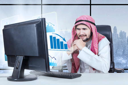 Picture of middle eastern male entrepreneur looking at a declining business graph on the monitor with winter background on the window photo