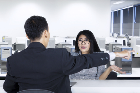 Male entrepreneur sacking a female worker in the office by pointing out photo