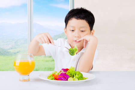 Little boy sitting at home and looks dislike a plate of vegetables salad photo