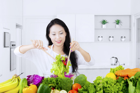Healthy young woman making and stirring a bowl of fresh vegetable in the kitchen at home photo
