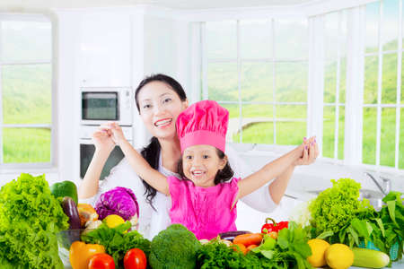 Portrait of cheerful little girl and her mother wearing a cooking hat with fresh vegetable on the table, shot in the kitchen photo