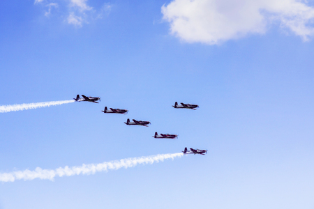 Image of six aircraft flying with smoke while doing airshow in the blue sky