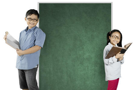 Two nerdy students reading a book while standing near a blank chalkboard, isolated on white background photo