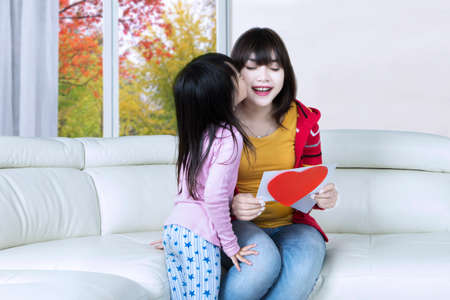 Little girl kiss her mother cheek after giving a greeting card on the sofa at home, shot with autumn background on the window photo