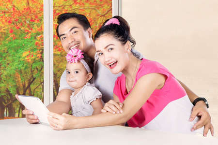 Portrait of cute child and young parents using digital tablet with autumn background on the window photo