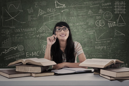 Beautiful female student looking up in classroom photo