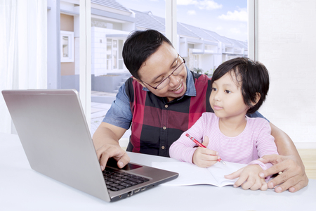 Picture of young father helping his cute daughter to studying while using a laptop at home photo