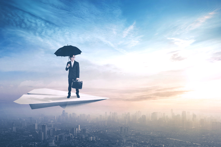 Male worker or a businessman standing on a paper plane while holding an umbrella and briefcase, flying above a city photo