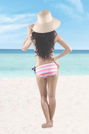 Summer Concept. Back view of a young woman with long hair, standing on the beach while wearing a striped bikini and a straw hat photo