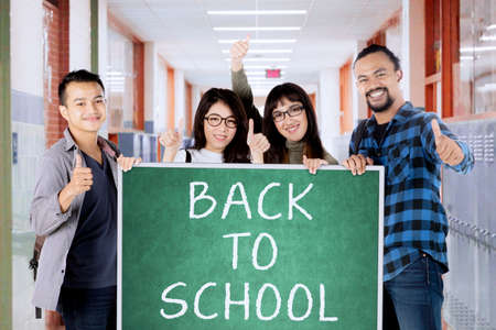 board: Multiracial of college students showing ok sign in the corridor while holding back to school word on the chalkboard