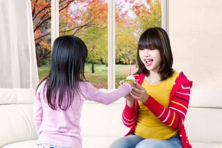 Portrait of a cheerful young woman receives a cupcake from her daughter, shot with autumn background on the window photo