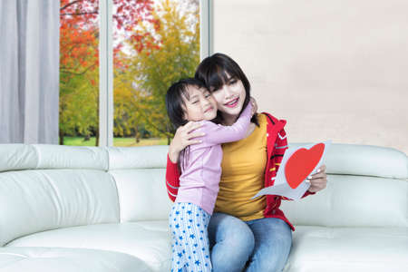 Little daughter embracing her mother on the sofa after giving a greeting card with heart symbol photo