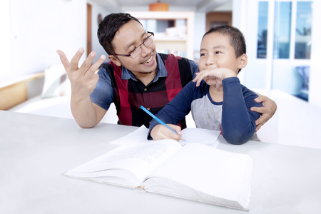 Photo of little boy learning to calculate with his father while doing homework and sitting in the living room photo