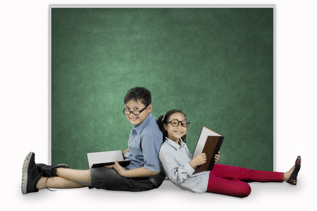 Picture of two elementary students looks happy while sitting near a blank chalkboard and holding a book in the studio photo