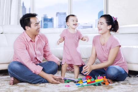 Picture of young Asian family is having fun together while playing with toys in the apartment photo