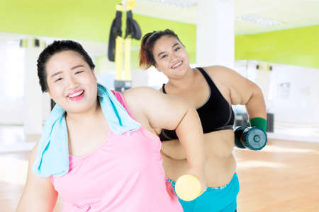 Two fat women wearing sportswear while lifting heavy dumbbells in the fitness center