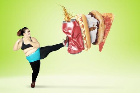 Concepto de dieta. Mujer joven con sobrepeso patea comidas rápidas y una lata de refresco mientras usa ropa deportiva. Disparo con fondo de pantalla verde Foto de archivo