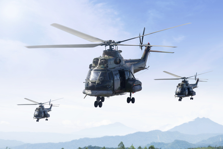 Three military helicopters flying in the blue sky while patrolling in the mountain Stock Photo