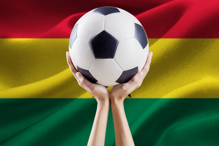 Soccer ball on the top of arms with national flag background of Ghana