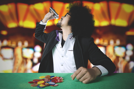 Young man betting his chip in a gambling while drinking whiskey at the casino
