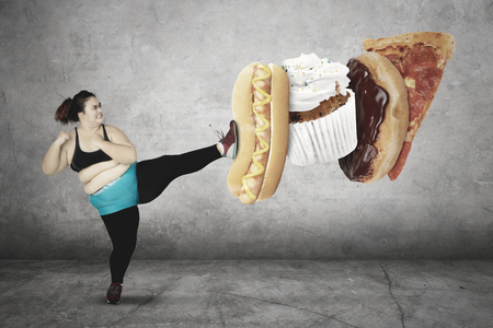 Diet concept. Overweight young woman wearing sportswear while kicking junk foods: a hot dog, cupcake, donut, and pizza
