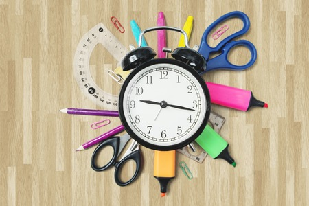Closeup of school supplies with an alarm clock on the wooden floor