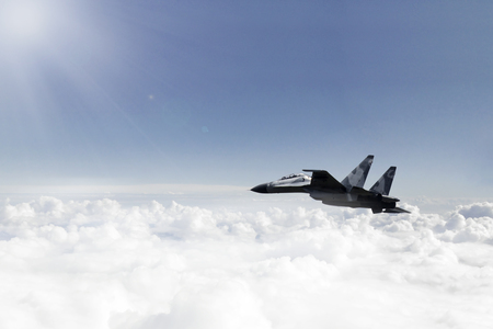 Image of a jet fighter flying over clouds in the blue sky