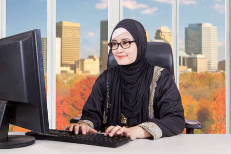 Beautiful Arab entrepreneur typing on a keyboard  and sitting in the office with autumn background on the window photo