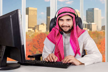 Portrait of young middle eastern male operator is typing on the keyboard while wearing headphones with autumn background on the window photo