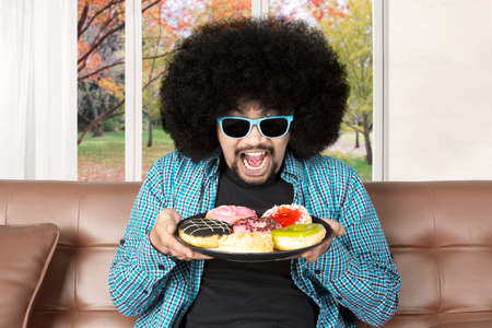 couch: Hungry Afro man with curly hair, holding a plate of donuts while sitting on the sofa and wearing sunglasses Stock Photo