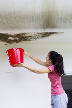 Portrait of Asian woman holding a bucket for collecting rainwater from damaged ceiling Foto de archivo