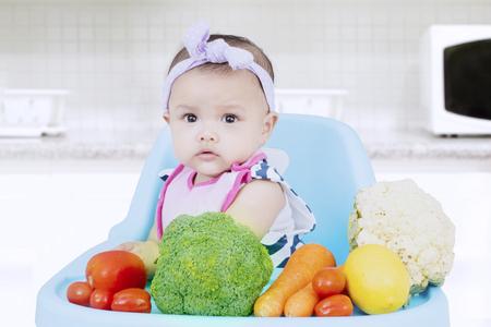 Portret van een mooi babymeisje die de camera met verse groenten op een hoge stoel in de keuken bekijken Stockfoto
