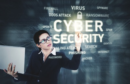 Image of pretty businesswoman holding a laptop computer while touching a text of cyber security on the virtual screen photo