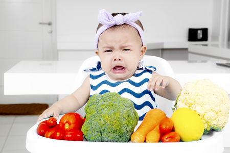 Picture of a sad baby girl making a pout face while sitting on the baby chair with fresh vegetables